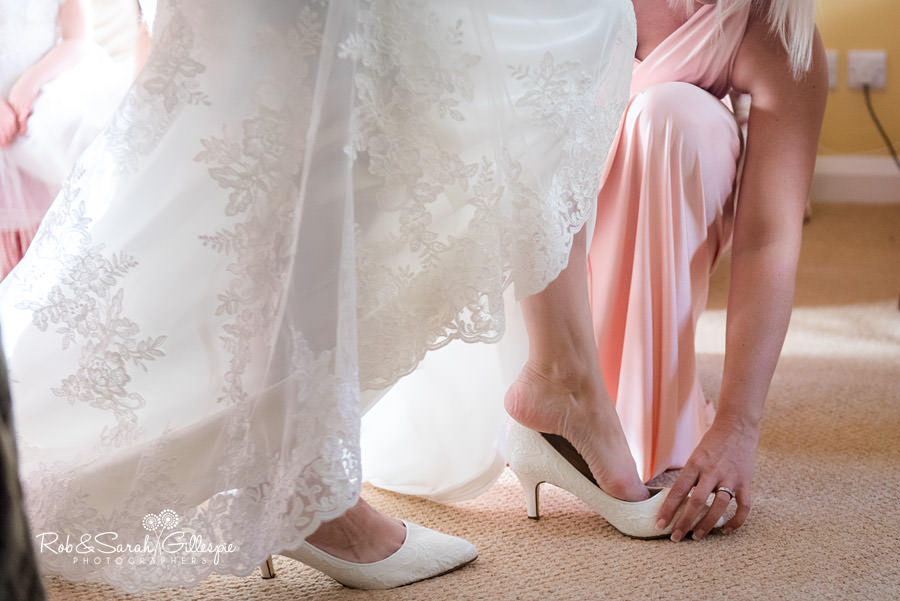 Bridesmaid helps bride put on shoes at Delbury Hall