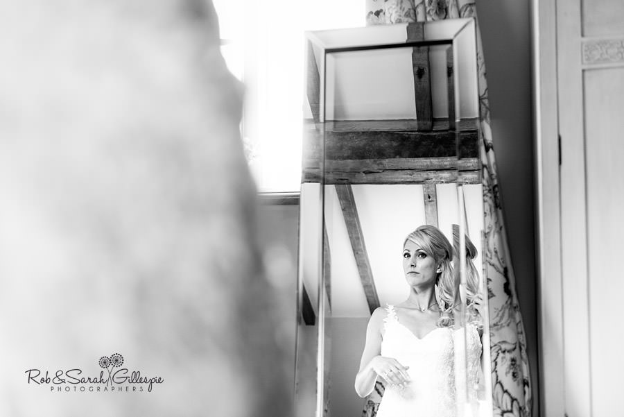Bride checks herself in mirror at Delbury Hall