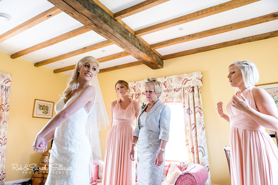 Bride and bridesmaids check dress before wedding at Delbury Hall