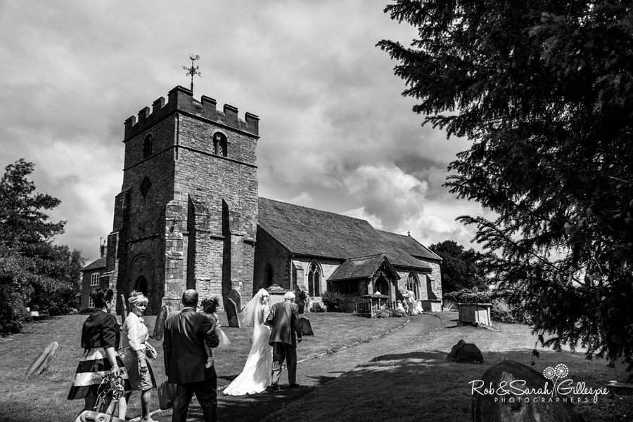 Bride and grandfather walk to church for wedding in Diddlebury Shropshire