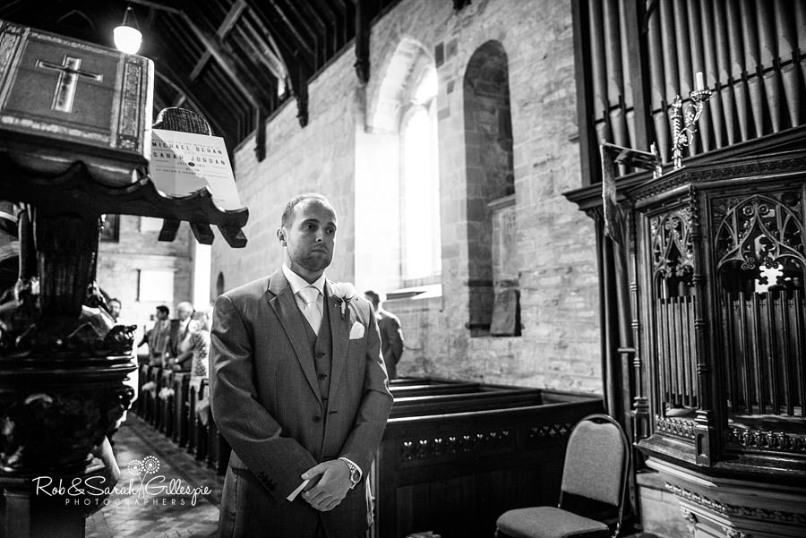 Groom awaits bride at wedding service in St Peters Church Diddlebury