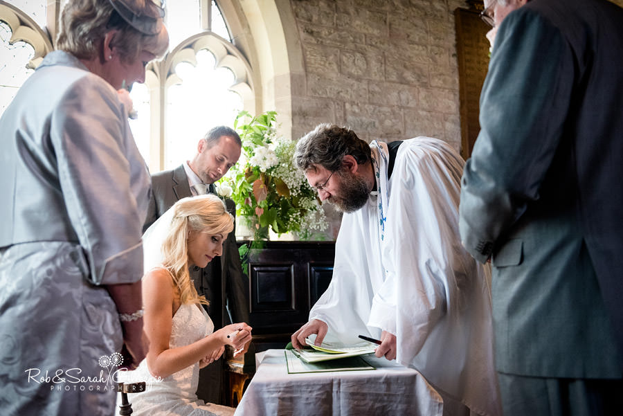 Bride and groom sign register during church wedding in Diddlebury
