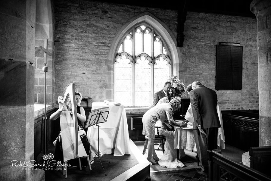 Wedding witnesses sign register as harpist plays