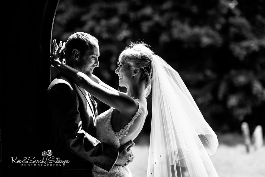 Bride and groom hug in doorway of church in striking sunlight