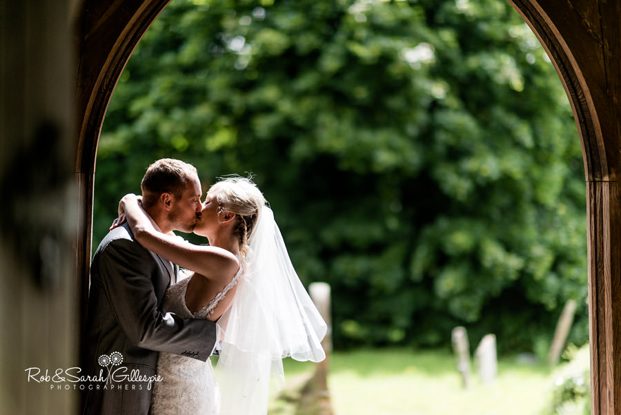 Bride and groom kiss in church doorway