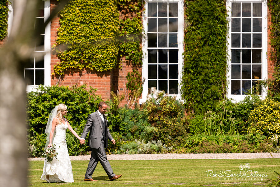 Bride and groom walk hand in hand at Delbury Hall