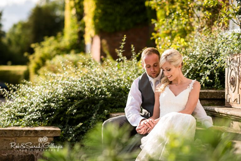 Bride and groom sitting on steps at Delbury Hall in sunshine