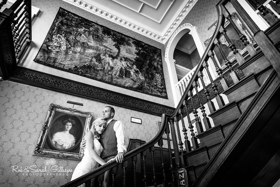 Bride and groom inside Delbury Hall on stairway