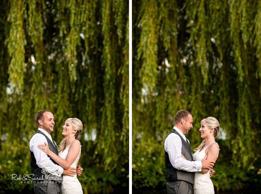 Bride and groom laughing together at Delbury Hall with weeping willow in background