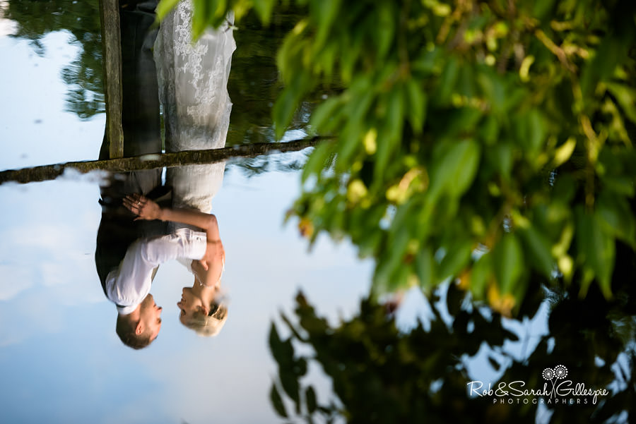 Reflection of bride and groom in water at Delbury Hall on beautiful summer evening