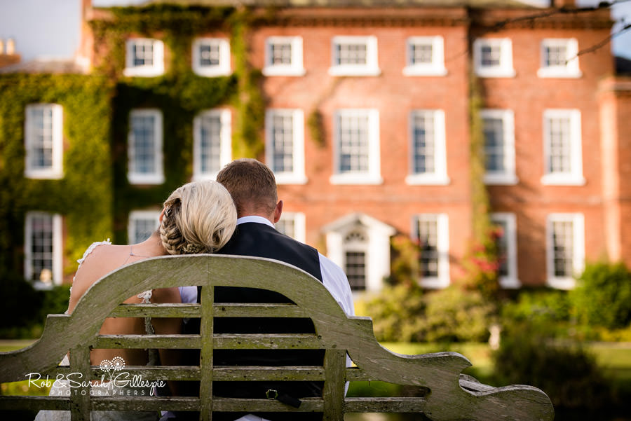 Bride and groom on bench with Delbury Hall in background in evening sunlight