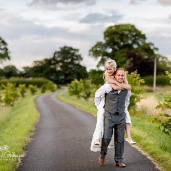 Bride and groom piggyback at Delbury Hall