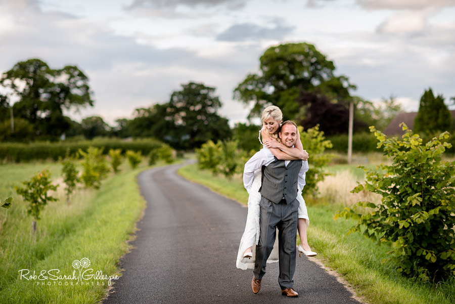 Bride and groom piggyback at Delbury Hall