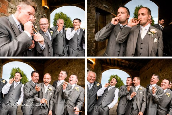 Groomsmen smoking cigars and laughing at Delbury Hall Wedding