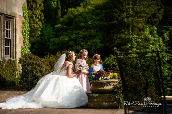 Groom and young girls look at flowers in garden at Coombe Abbey