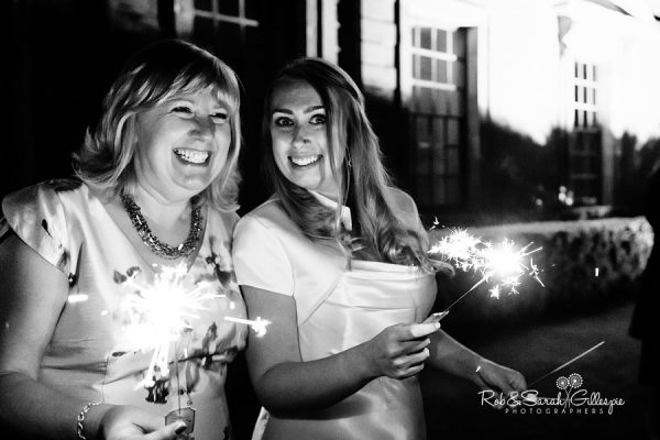 Bride and friend playing with sparklers at Coombe Abbey wedding