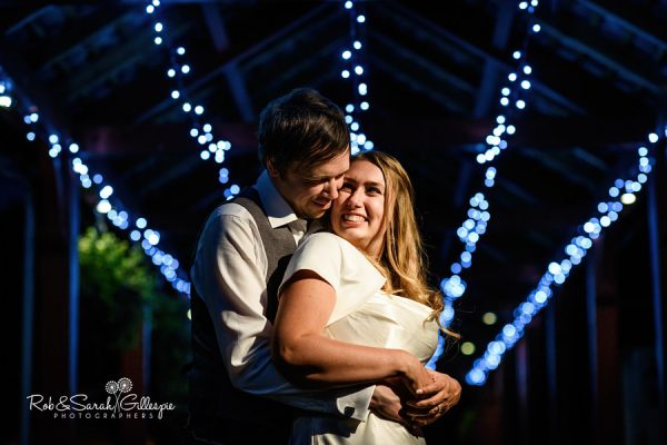 Bride and groom under lights at Coombe Abbey