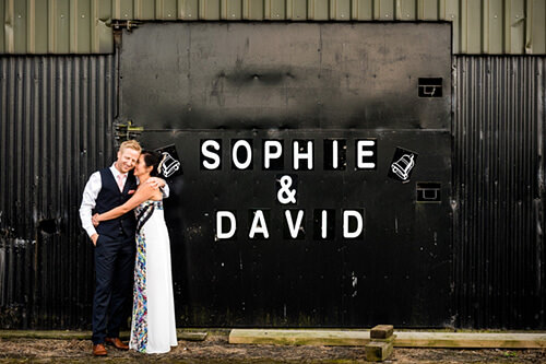 Bride and groom together in front of barns doors with their names painted on