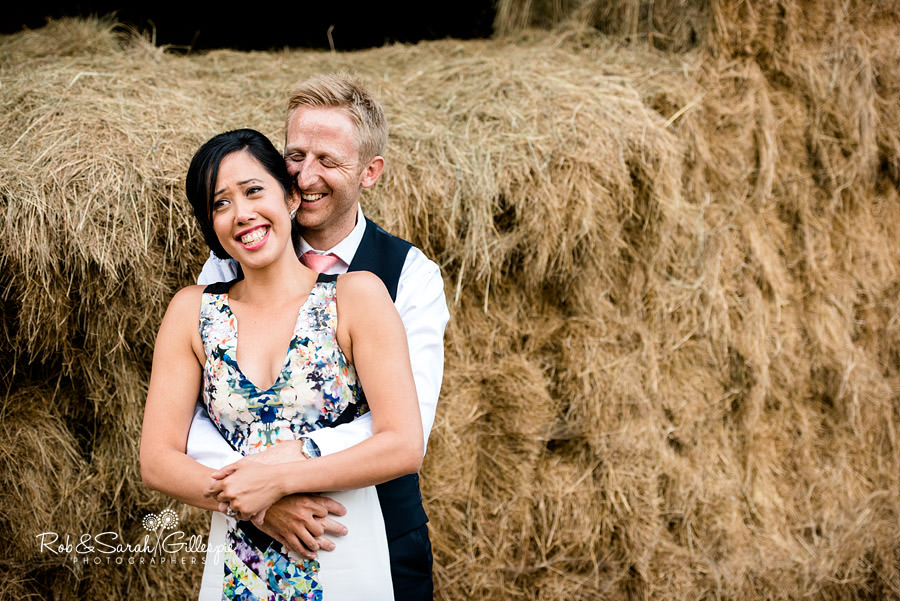 Bride and groom laughing together in front of hay bales