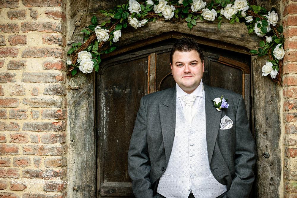 Portrait of groom in doorway at Gorcott Hall