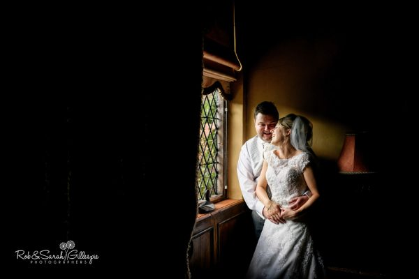 Bride and groom in window light at Gorcott Hall