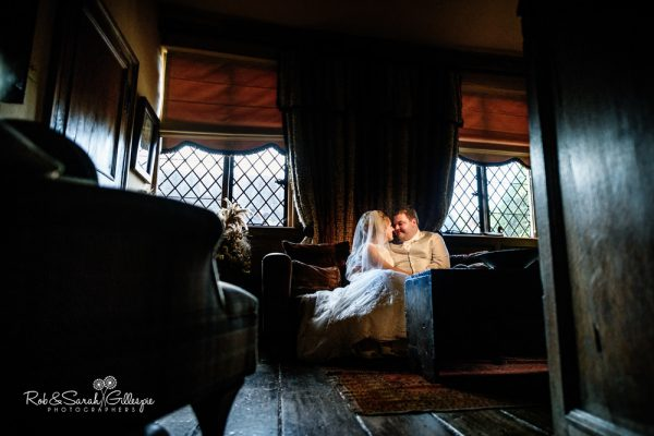 Bride and groom sitting together inside Gorcott Hall