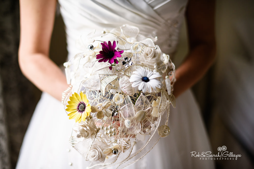Close up of bride's bouquet, made of ornate pieces and real flowers