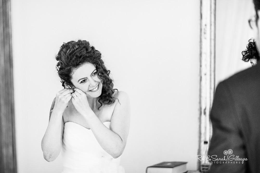 Bride smiling as she fastenes earrings