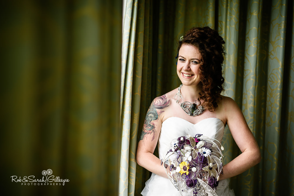Portrait of bride laughing in window light before wedding