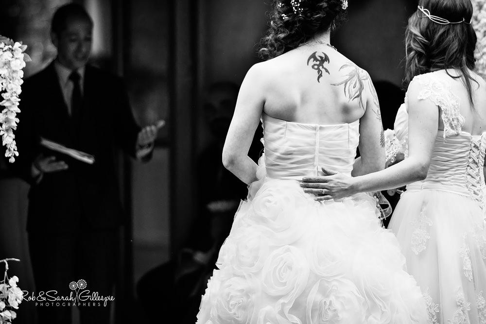 Bride rests her hand on her bride during same-sex wedding ceremony