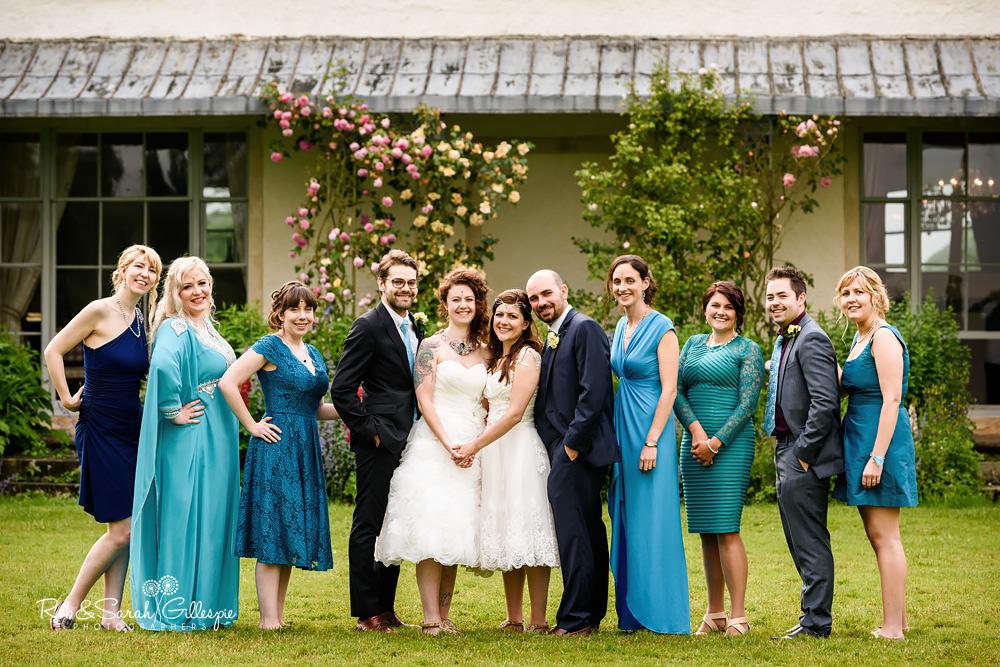 Brides, bridesmaids and ushers group photo at same-sex wedding