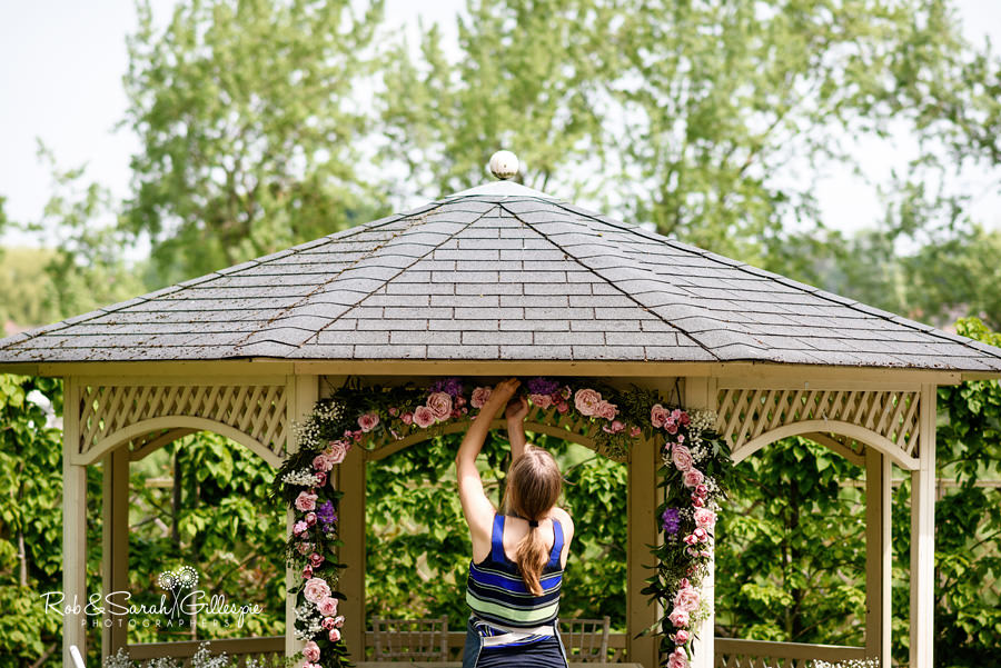 Florist putting up flowers for outdoor wedding ceremony at Warwick House