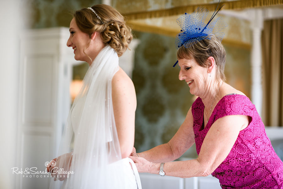 Bride getting into wedding dress at Warwick House