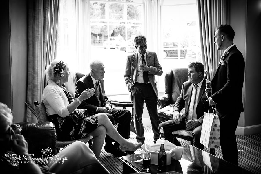 Groom chats to wedding guests at Warwick House