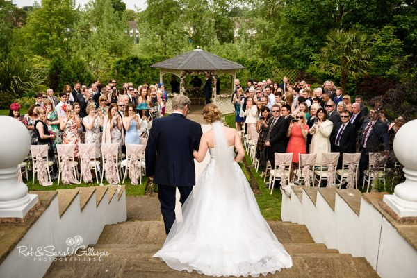 Bride makes her entrance to wedding ceremonmy at Warwick House