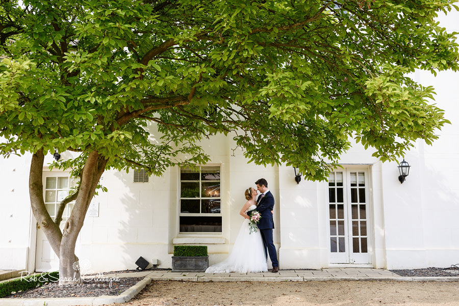Bride and groom together under magnolia tree at Warwick House