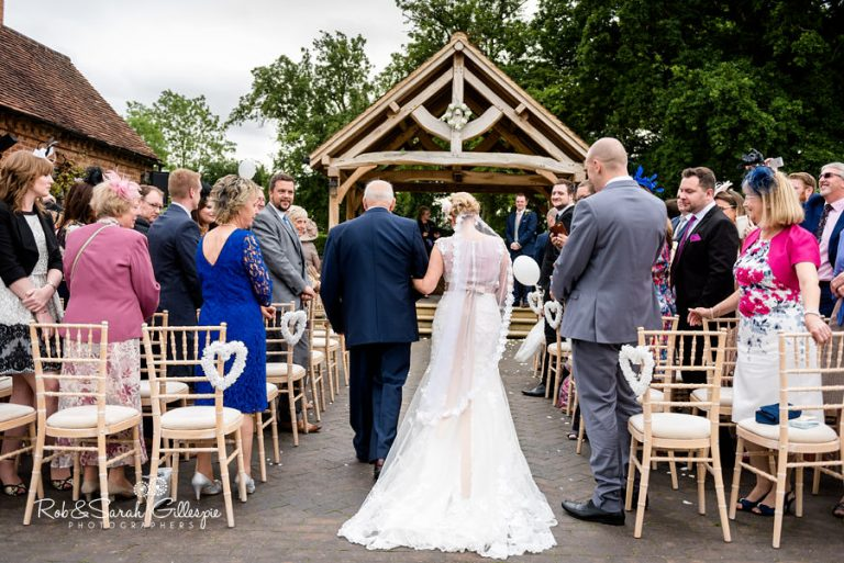 Bride and father walk up aisle for outdoor wedding ceremony at Wethele Manor