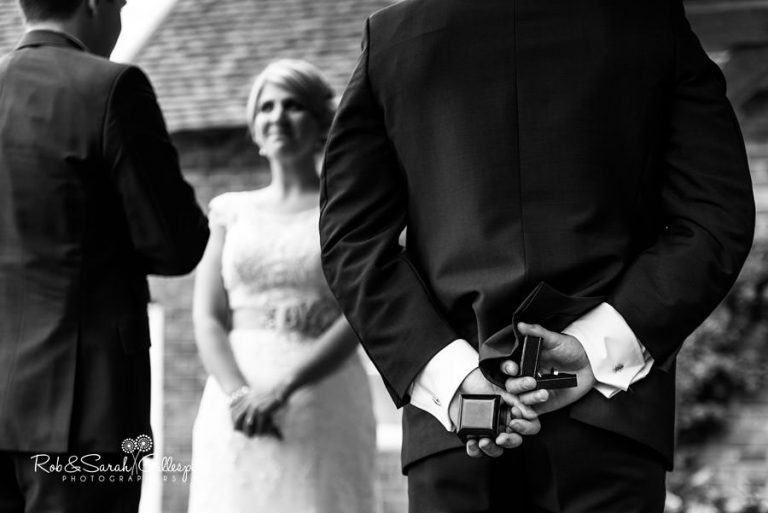 Best man holds rings during outdoor wedding ceremony