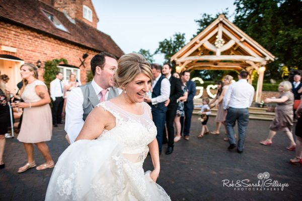 Bride, groom and wedding guests dancing outside at Wethele Manor