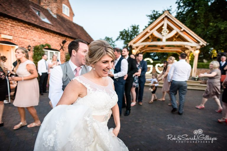 Bride, groom and wedding guests dancing outside at Wethele Manor in Warwickshire