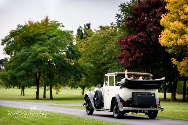 Bride and groom arrive at Alrewas Hayes in open-top car
