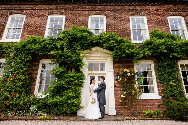 Bride and groom in front of house at Alrewas Hayes wedding venue