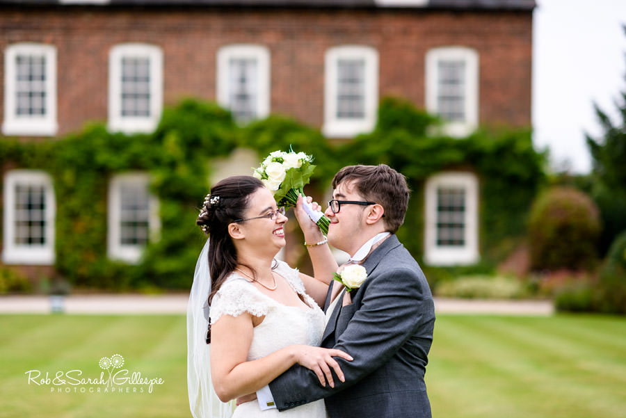 Bride and groom laughing in front of farm house at Alrewas Hayes