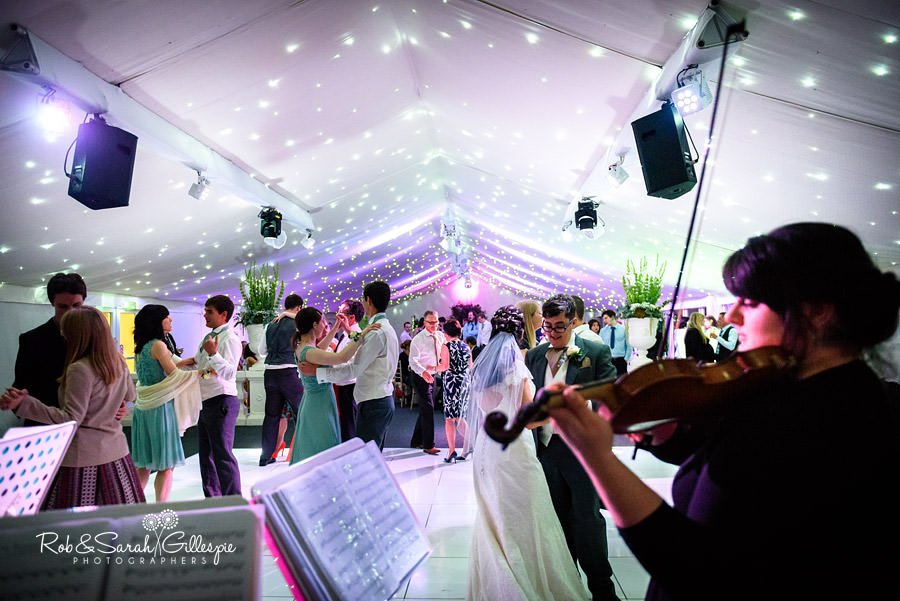 Musicians play while wedding guests dance at Alrewas Hayes