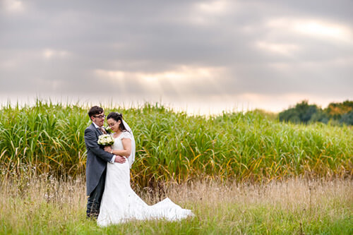 Bride and groom together in crop field at Alrewas Hayes with beautiful evening sky