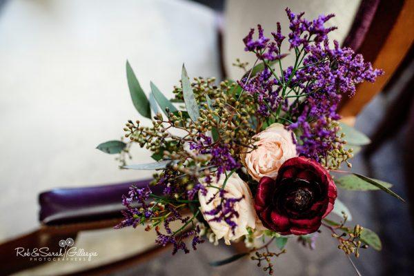 Wedding flowers on chair at Brockencote Hall