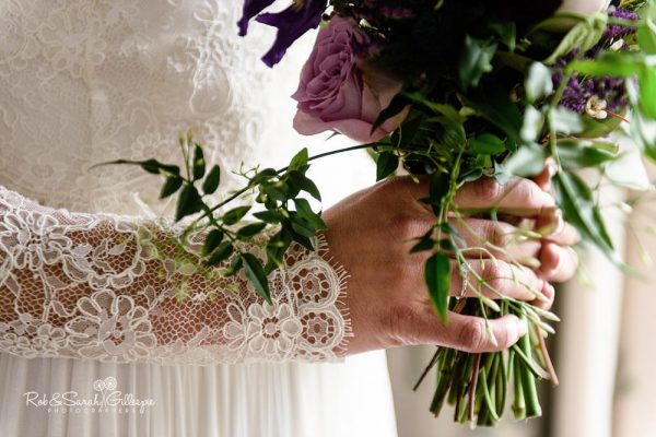 Detail of bridal bouquet and wedding dress at Brockencote Hall