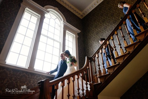Bride walks down staircase at Brockencote Hall wedding