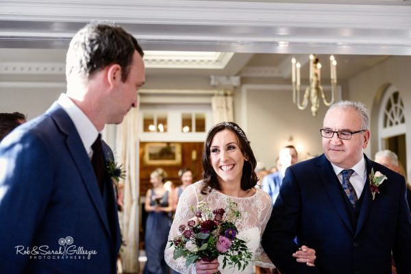 Bride and groom exchange a smile at Brockencote Hall civil wedding ceremony