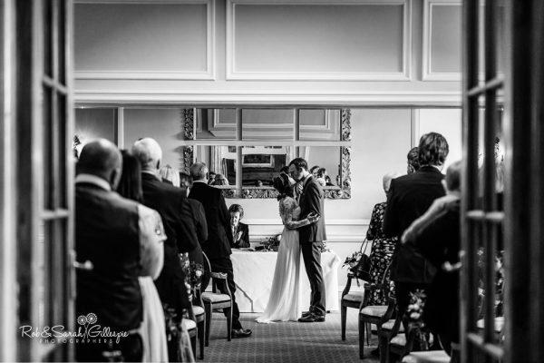 Bride and groom kiss during wedding at Brockencote Hall